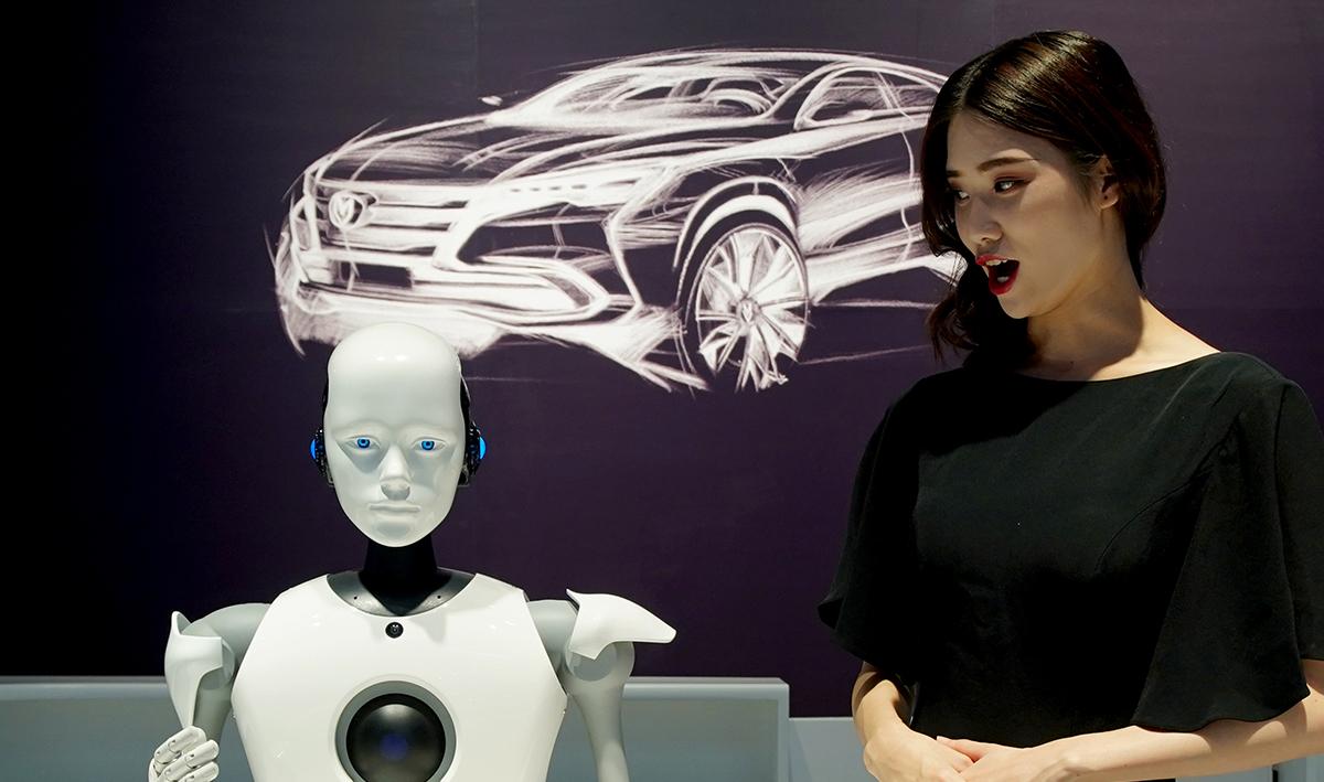長安汽車展臺上一個機器人和接待咨詢人員交流