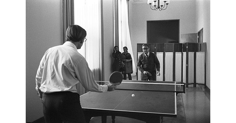 """1971年10月26日,執掌美國國家安全委員會的總統國家安全顧問基辛格博士(Kissinger)(正對鏡頭帶黑邊眼鏡)秘密訪華,與其助手(後任駐華大使)溫斯頓勳爵(Winston Lord)(背對鏡頭)在駐地打乒乓球。次年2月21日,美國總統尼克松首次訪華,隨後于上海發表《聯合公報》。這場由中國邀請美國乒乓球隊訪華開始的""""乒乓外交"""",打開了隔絕22年的中美交往大門。"""