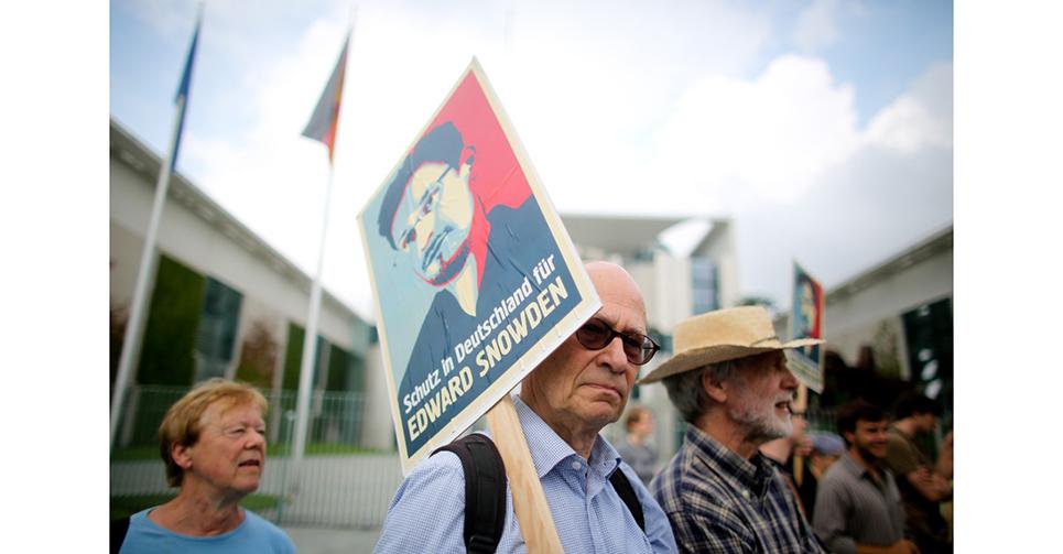 """愛德華·斯諾登(Edward Snowden)生于1983年,曾是CIA(美國中央情報局)技術分析員,後供職于國防項目承包商Booz Allen Hamilton。2013年6月,他將美國國家安全局關于""""棱鏡""""(PRISM)監聽項目的秘密文檔披露給了《衛報》和《華盛頓郵報》,隨即遭美國政府通緝.  圖為德國民眾于街頭遊行,聲援斯諾登。"""