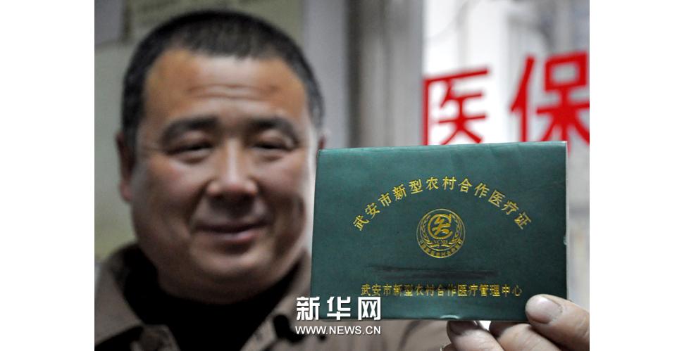 2013年3月25日,一名農民在河北省邯鄲市第二醫院展示他的新型農村合作醫療證。新華社發