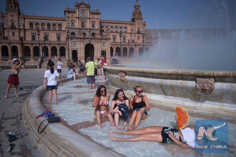 Girls Cool Off In A Fountain Of The Plaza De Espana In Sevilla During A  Heat Wave, On July 12, 2017. (AFP/ JORGE)