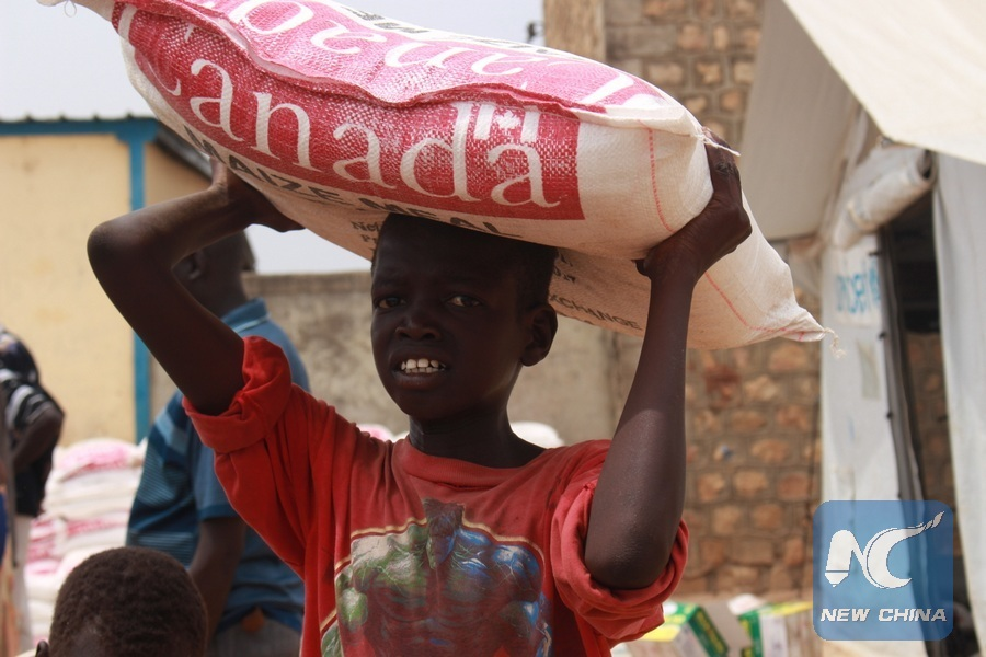 Over 1000 foreigners risk losing jobs in s sudan over work permit an internally displaced person idp carries a sack of maize flour donated by humanitarian organizations at mahad camp in central juba south sudan publicscrutiny Image collections