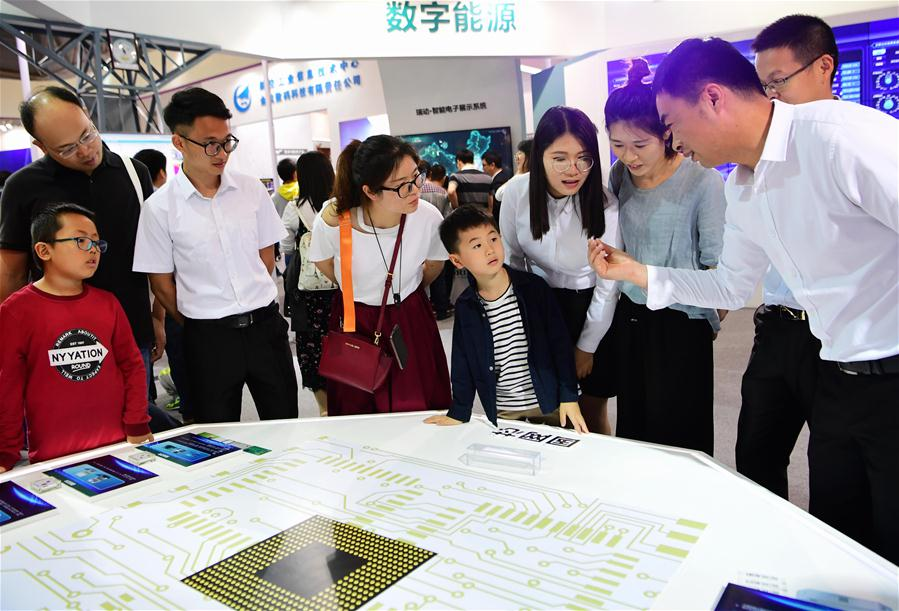 Visitors learn the research process of a chip from the State Grid Corporation of China during the Digital China Exhibition in Fuzhou, capital of southeast China's Fujian Province, April 22, 2018. The exhibition opened to the public on Sunday, during which 293 exhibitors displayed the latest digital technology. (Xinhua/Wei Peiquan)<br/>