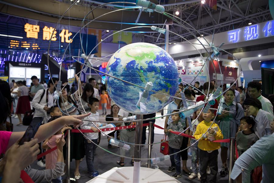 Visitors look at a model of satellite system during the Digital China Exhibition in Fuzhou, capital of southeast China's Fujian Province, April 22, 2018. The exhibition opened to the public on Sunday, during which 293 exhibitors displayed the latest digital technology. (Xinhua/Jin Liwang)<br/>