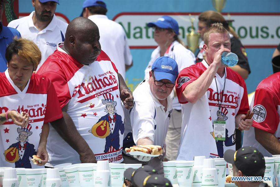 A staff member offers hot dogs as eaters compete in the men's competition of the Nathan's Hot Dog Eating Contest at Coney Island of New York, the United States, on July 4, 2018. Joey Chestnut set a new world record Wednesday by devouring 74 hot dogs in 10 minutes at the Nathan's Hot Dog Eating Contest in New York. Miki Sudo defended the women's title by eating 37 hot dogs in 10 minutes. (Xinhua/Wang Ying)<br/>