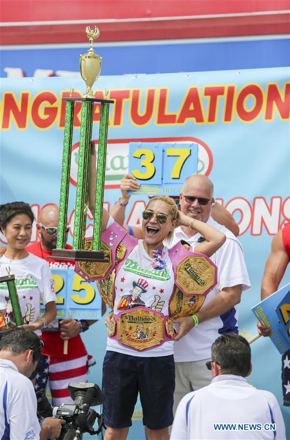 Miki Sudo (C) celebrates after winning the women's competition of the Nathan's Hot Dog Eating Contest at Coney Island of New York, the United States, on July 4, 2018. Joey Chestnut set a new world record Wednesday by devouring 74 hot dogs in 10 minutes at the Nathan's Hot Dog Eating Contest in New York. Miki Sudo defended the women's title by eating 37 hot dogs in 10 minutes. (Xinhua/Wang Ying)<br/>