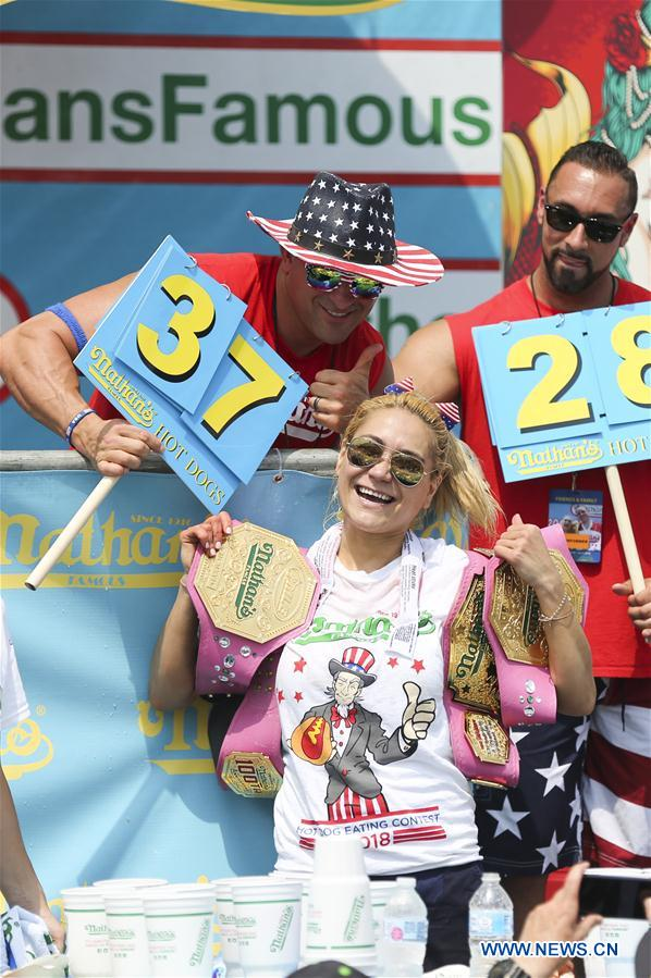 Miki Sudo (C, Front) celebrates after winning the women's competition of the Nathan's Hot Dog Eating Contest at Coney Island of New York, the United States, on July 4, 2018. Joey Chestnut set a new world record Wednesday by devouring 74 hot dogs in 10 minutes at the Nathan's Hot Dog Eating Contest in New York. Miki Sudo defended the women's title by eating 37 hot dogs in 10 minutes. (Xinhua/Wang Ying)<br/>