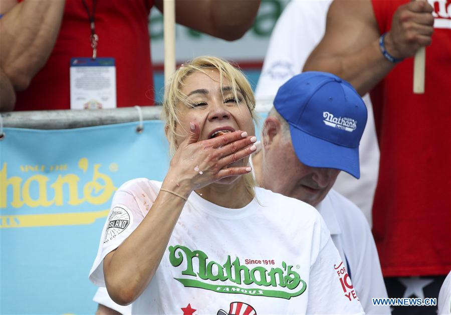 Miki Sudo (Front) competes during the women's competition of the Nathan's Hot Dog Eating Contest at Coney Island of New York, the United States, on July 4, 2018. Joey Chestnut set a new world record Wednesday by devouring 74 hot dogs in 10 minutes at the Nathan's Hot Dog Eating Contest in New York. Miki Sudo defended the women's title by eating 37 hot dogs in 10 minutes. (Xinhua/Wang Ying)<br/>