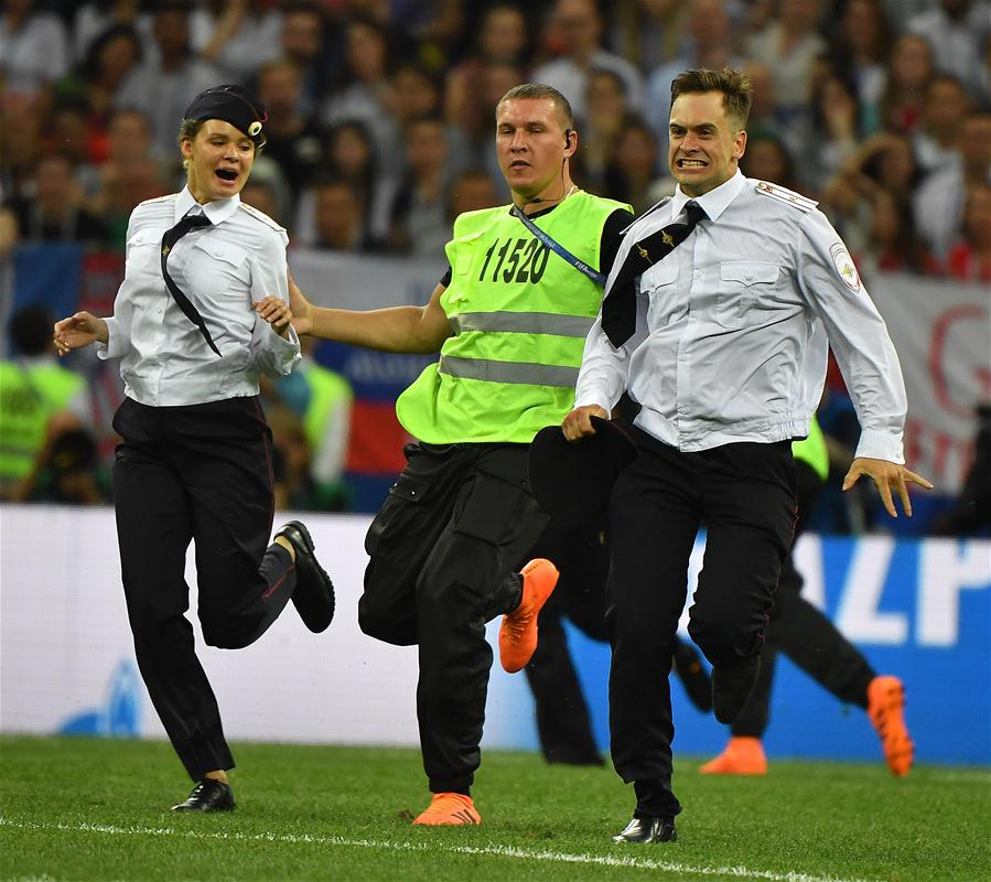 Pitch invaders are chased by stewards during the 2018 FIFA World Cup final match between France and Croatia in Moscow, Russia, July 15, 2018. (Xinhua/Li Ga)<br/>