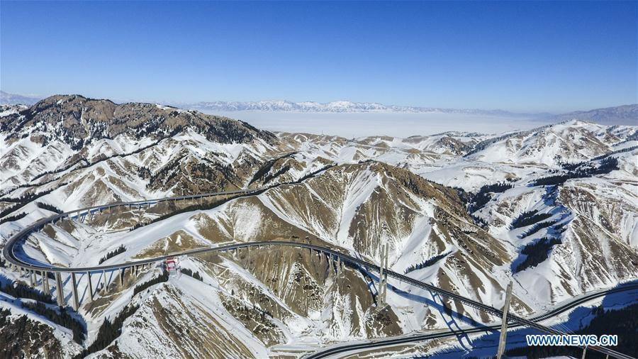 Aerial photo taken on Jan. 26, 2018 shows the Lianyungang-Horgos expressway along the Tianshan Mountains, northwest China's Xinjiang Uygur Autonomous Region. As an important link of the Silk Road Economic Belt, Xinjiang is speeding up the development of transportation and logistics to connect east and west. By the end of 2017, the total length of roads in Xinjiang reached 186,000 km, with 4,578 km of expressways. (Xinhua/Hu Huhu)<br/>