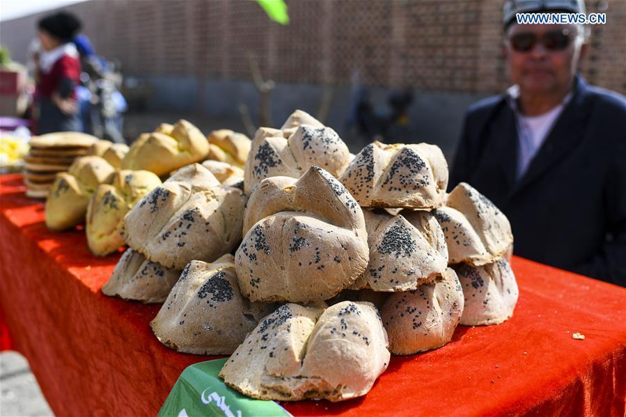 A vendor sells Nang, a kind of crusty cake, at a bazaar in Turpan, northwest China's Xinjiang Uygur Autonomous Region, March 14, 2017. (Xinhua/Wang Fei)<br/>