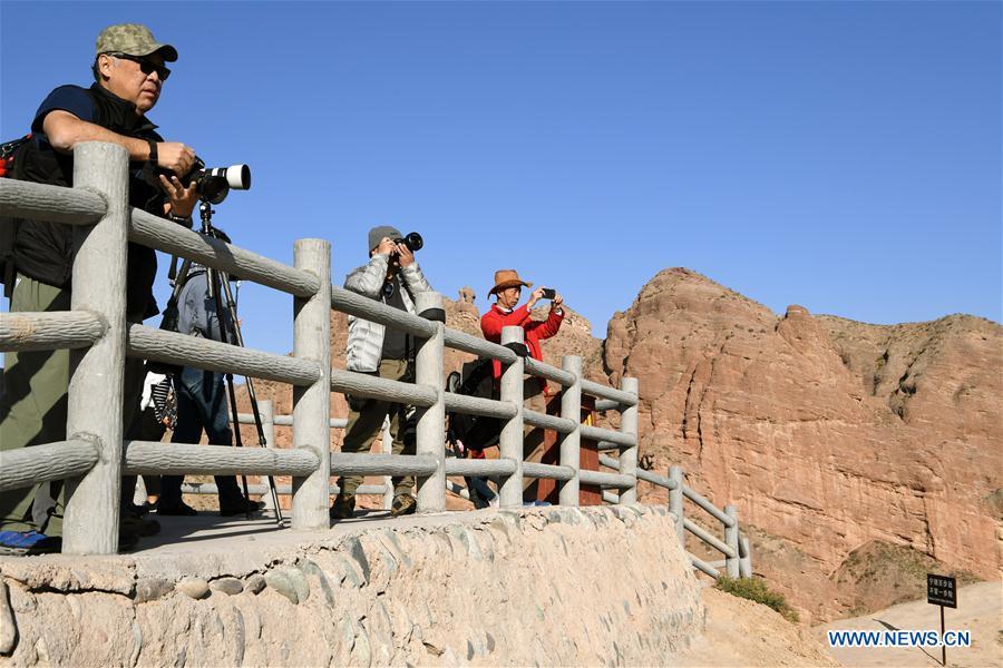 Tourists visit Danxia landform at Binggou scenic area in China\'s ...