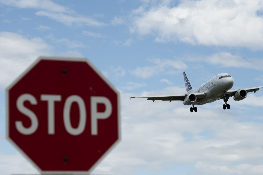 Photo taken on March 10, 2020 shows a stop sign and a plane approaching to land at Ronald Reagan Washington National Airport in Arlington, Virginia, the United States.(Xinhua/Liu Jie)