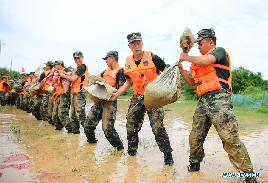 Armed Policemen Move Sand Bags for Dyke Reinforcement in Poyang County, Jiangxi