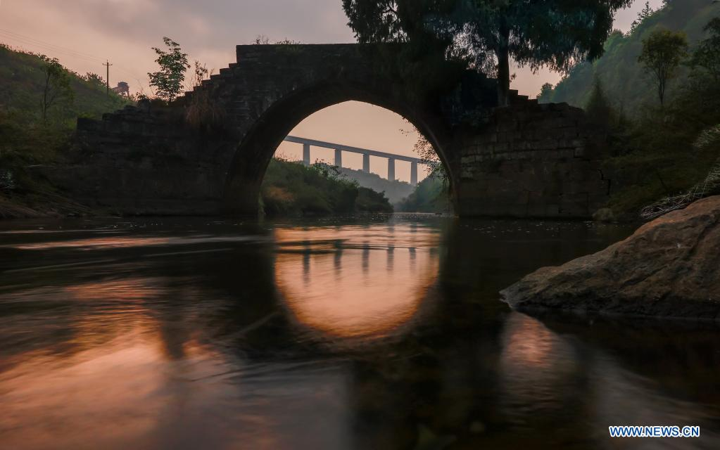 The Mengjia ancient bridge, built in 1882, is pictured along with the Yinpo River grand bridge of the Guiyang-Nanning high-speed railway (in the distance) in Dushan County, southwest China's Guizhou Province, April 1, 2021. (Xinhua/Liu Xu)