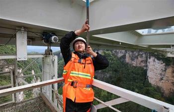 Female cleaner overcomes fear for cleaning bridge bottom in Zhangjiajie scenic spot, China's Hunan