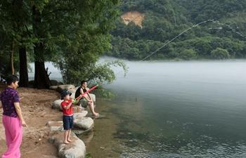 People enjoy coolness by Xin'an River in Jiande, E China's Zhejiang