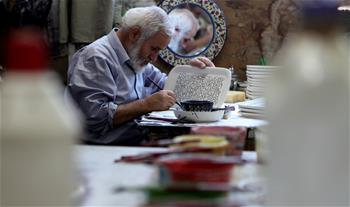 Palestinian artist works at glass, ceramics factory in West Bank city of Hebron