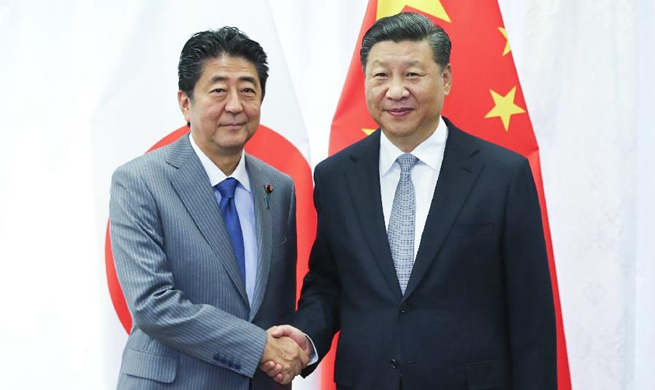 Xi, Abe meet on further improving China-Japan ties