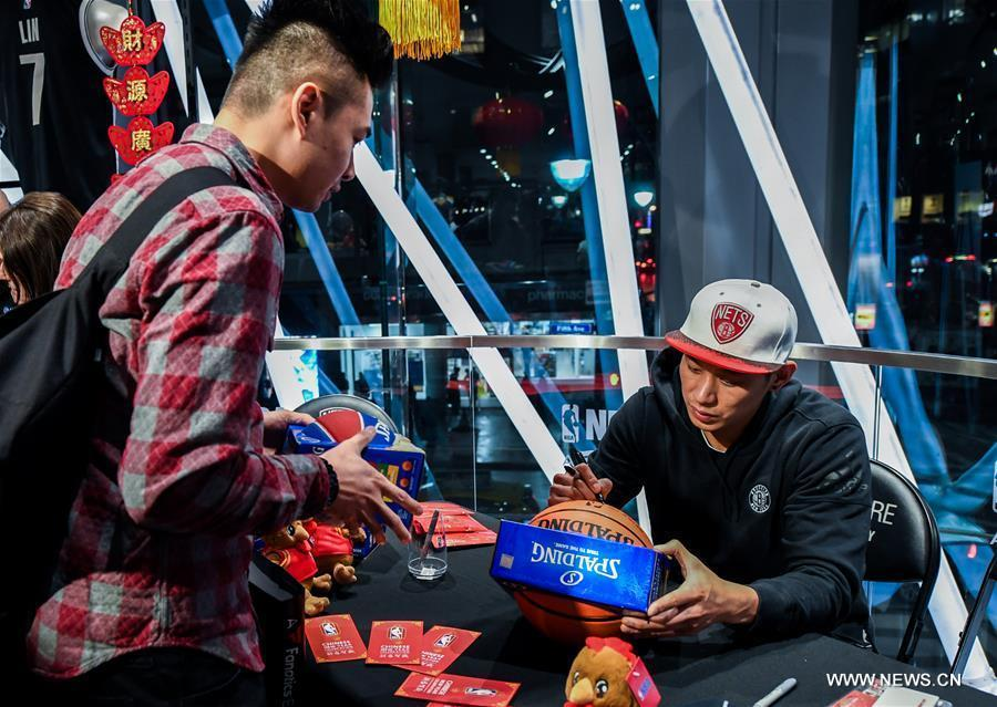 Brooklyn Nets guard Jeremy Lin (R) signs autograph for a fan at a Chinese New Year celebration at the NBA store on Manhattan 5th Avenue, New York City, the United States, on Jan. 24, 2017. Brooklyn Nets guard Jeremy Lin said on Monday he expected to be back to action in 3-5 weeks from his left hamstring injury. (Xinhua/Li Rui)