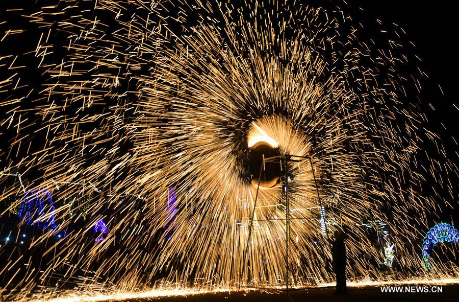 Sparks pour down as performers spray burning hot iron water to simulate display of fireworks at Neihuang County, central China's Henan Province, Feb. 1, 2017. (Xinhua/Li Gang)