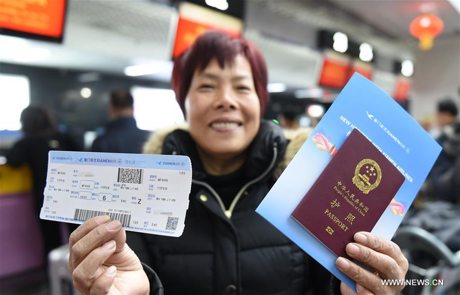 A passenger of MF849 shows her ticket at the Fuzhou International Airport in Fuzhou, capital of southeast China's Fujian Province, Feb. 15, 2017. MF849, the first direct flight of Xiamen Airlines from Fuzhou to New York, took off here on Wednesday. (Xinhua/Lin Shanchuan)
