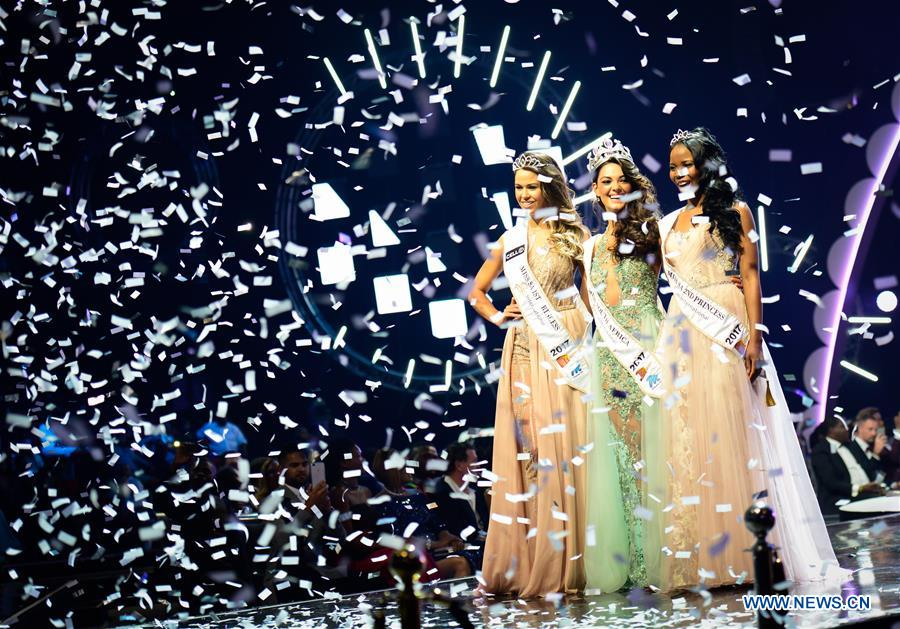 The first prize winner Demi-Leigh Nel-Peters (C), the first runner-up Ade van Heerden (L) and the second runner-up Boipelo Mabe pose for photos during the Miss South Africa 2017 Pageant and Celebration in Sun City, North West Province, South Africa, on March 26, 2017. The Miss South Africa 2017 Pageant and Celebration was held here Sunday. Demi-Leigh Nel-Peters from Sedgefield in the Western Cape Province, a 21-year-old part-time model, was crowned Miss South Africa 2017 with a prize of one million rand (about 80,000 US dollars), and the runners-up are Ade van Heerden (1st Princess) from the Western Cape Province and Boipelo Mabe (2nd Princess) from Gauteng Province. (Xinhua/Zhai Jianlan)