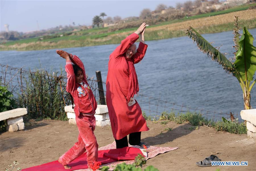 Lady Didi (R) teaches an Egyptian girl yoga at her Nile River School in Ayyat district on the outskirts of Giza Province, about 100 km south of Cairo, capital of Egypt, on March 26, 2017. Diana Sandor, known as Didi, an old Hungarian-born German-raised woman, covered the long distance from West to East six years ago to open her Nile River School as a charitable kindergarten and educational center at the heart of remote, impoverished Baharwa village of Ayyat district on the outskirts of Giza Province, about 100 km south of the Egyptian capital Cairo. Didi said she started building the center 'brick by brick,' through little donations from friends and volunteers around the world and that she is concerned with 'teaching children life,' not just languages and skills. (Xinhua/Ahmed Gomaa)