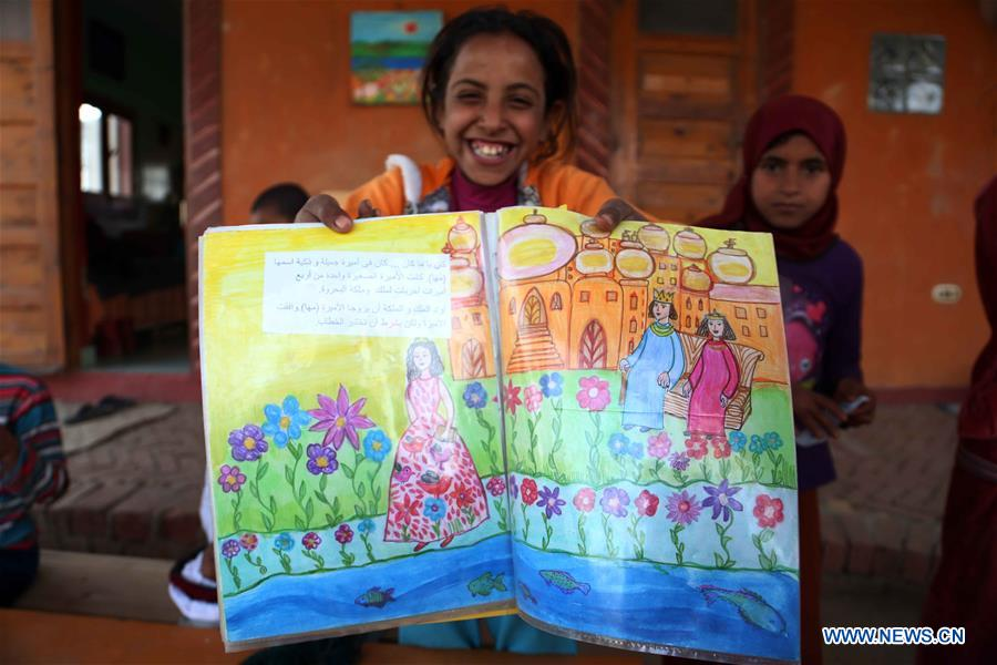 An Egyptian girl displays her painting work at lady Didi's Nile River School in Ayyat district on the outskirts of Giza Province, about 100 km south of Cairo, capital of Egypt, on March 26, 2017. Diana Sandor, known as Didi, an old Hungarian-born German-raised woman, covered the long distance from West to East six years ago to open her Nile River School as a charitable kindergarten and educational center at the heart of remote, impoverished Baharwa village of Ayyat district on the outskirts of Giza Province, about 100 km south of the Egyptian capital Cairo. Didi said she started building the center 'brick by brick,' through little donations from friends and volunteers around the world and that she is concerned with 'teaching children life,' not just languages and skills. (Xinhua/Ahmed Gomaa)