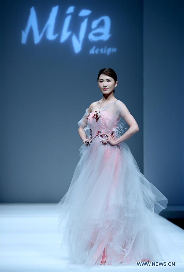 A model presents a creation designed by Lyu Qing during China Fashion Week in Beijing, capital of China, March 27, 2017.