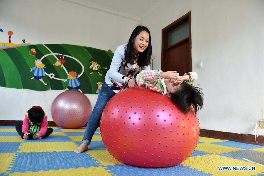 Teacher Li Xiaojiao works during a sensory integration training for autistic children at a service center of the Lingxing community in Taiyuan, capital of north China's Shanxi Province, March 29, 2017. Established in 2010, the service center has accommodated over 60 children with autism. A total of 29 teachers take part in the rehabilitation program to help these children. April 2 marks the World Autism Awareness Day. (Xinhua/Zhan Yan)