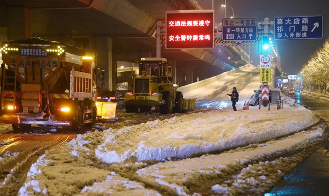 Staff members clear off snow in E China