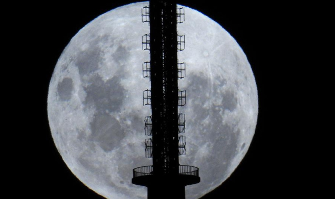 Moon rises behind Telstra Telecom Tower in Canberra, Australia
