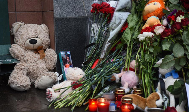 Flowers and dolls placed to mourn victims of Russia's shopping mall fire