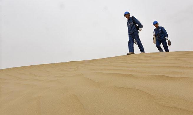 Linemen patrol power line across Taklimakan Desert in China's Xinjiang