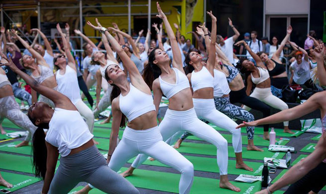 People participate in free yoga class to celebrate solstice in New York