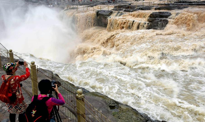 Tourists view Hukou Waterfall on Yellow River