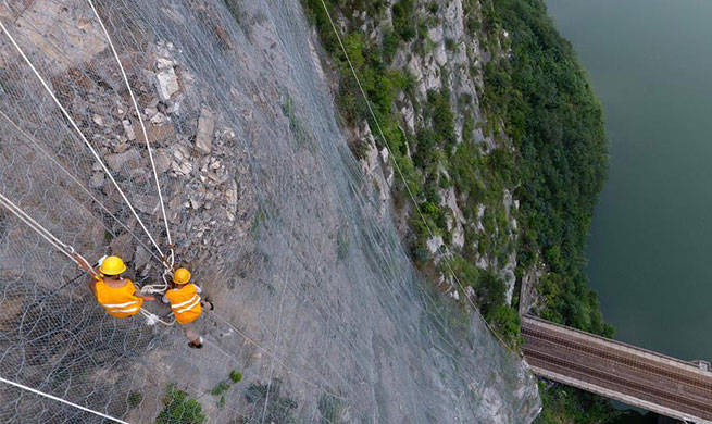 People work on cliff to ensure railway safety in C China's Henan