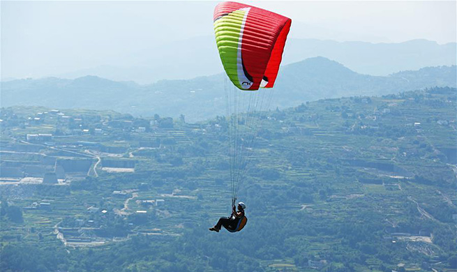 Tourists experience paragliding at Gujian Mountain scenic area in SW China's Chongqing