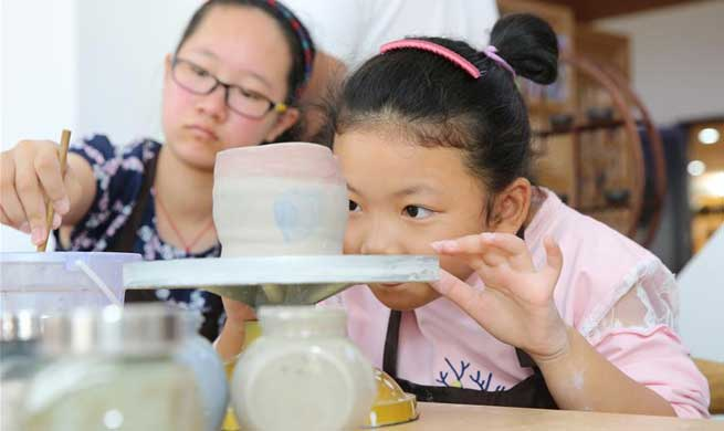 Children learn to make ceramics during National Day holiday in China's Jiangsu