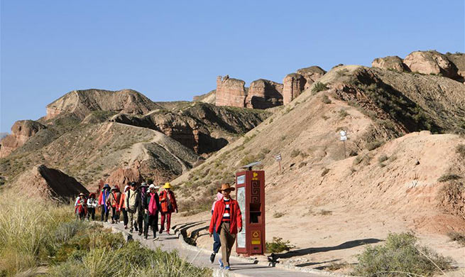 Tourists visit Danxia landform at Binggou scenic area in China's Gansu