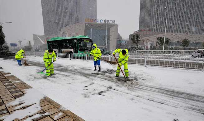 People clear accumulated snow to avoid traffic disruption in parts of China