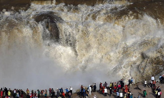 People enjoy scenery at Hukou Waterfall in China's Shanxi