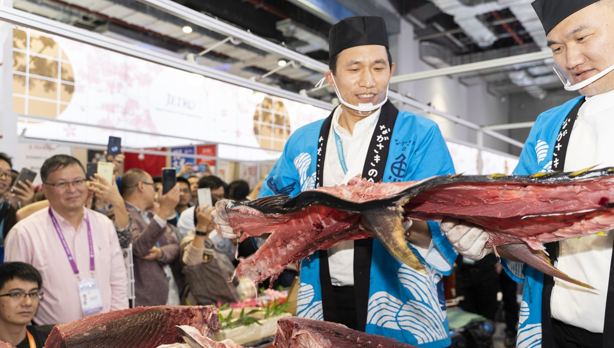 Staff members of Japanese company prepare bluefin tuna meat for visitors at 2nd CIIE