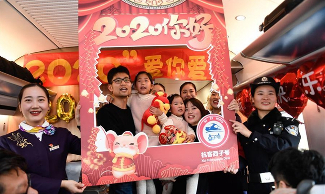 Staff members, passengers aboard train G20 celebrate upcoming New Year