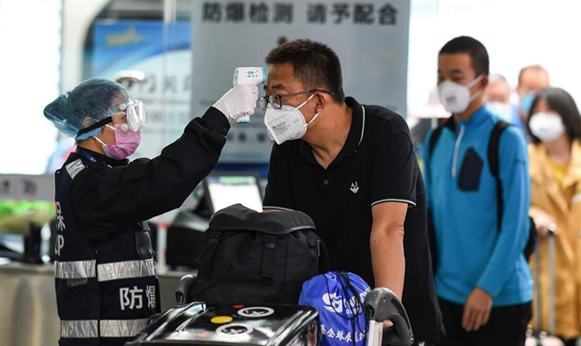 Passengers accept temperature checks at Sanya Phoenix Int'l Airport, Hainan