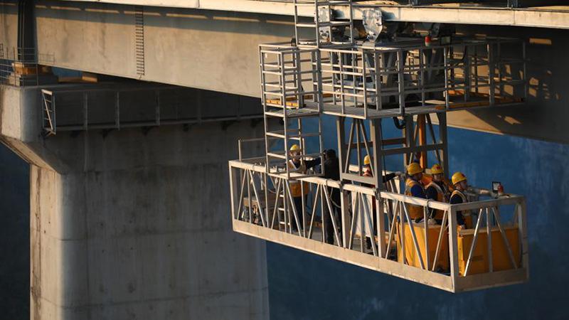 Maintenance workers work on Xixi River Grand Bridge in Guizhou
