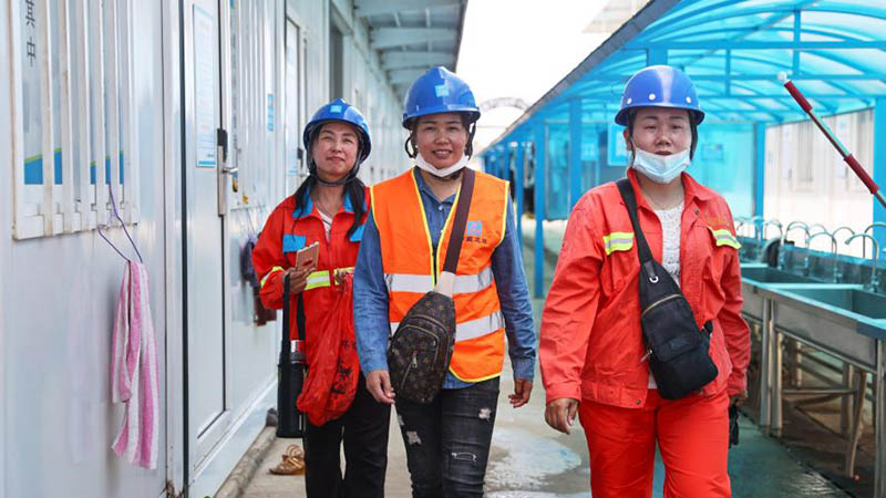 Female tower crane operators work at construction site of shopping mall