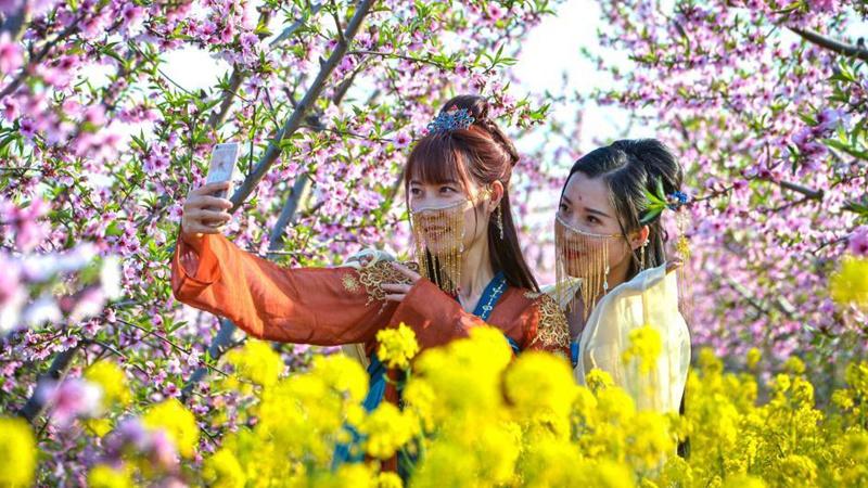 Tourists enjoy flowers at peach garden in Hebei