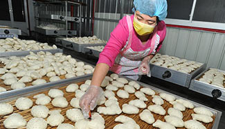 Cooks make traditional steamed buns for Spring Festival, N China